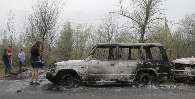Local residents inspect burnt out cars after a night fight at the check point which was under the control of pro-Russian activists in the village of Bulbasika near Slovyansk, Ukraine, Sunday, April 20, 2014. At least one person was killed in the clash. Pro-Russian insurgents defiantly refused to surrender their weapons or give up government buildings in eastern Ukraine, despite a diplomatic accord reached in Geneva and overtures from the government in Kiev. (AP Photo/Efrem Lukatsky)