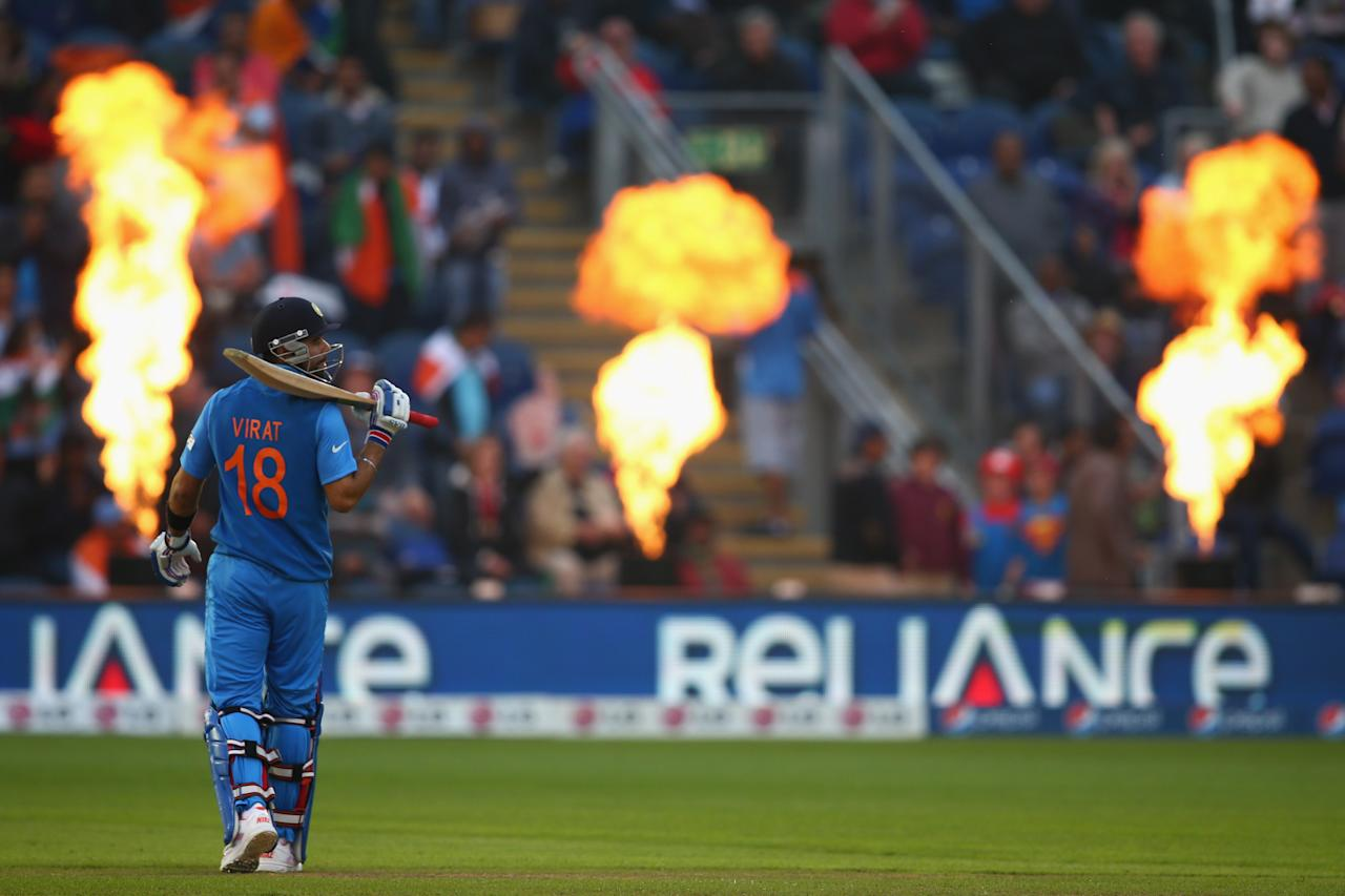 CARDIFF, WALES - JUNE 20: Virat Kohli of India stands alone as the pirotechnics explode during the ICC Champions Trophy Semi-Final match between India and Sri Lanka at the SWALEC Stadium on June 20, 2013 in Cardiff, Wales.  (Photo by Michael Steele/Getty Images)