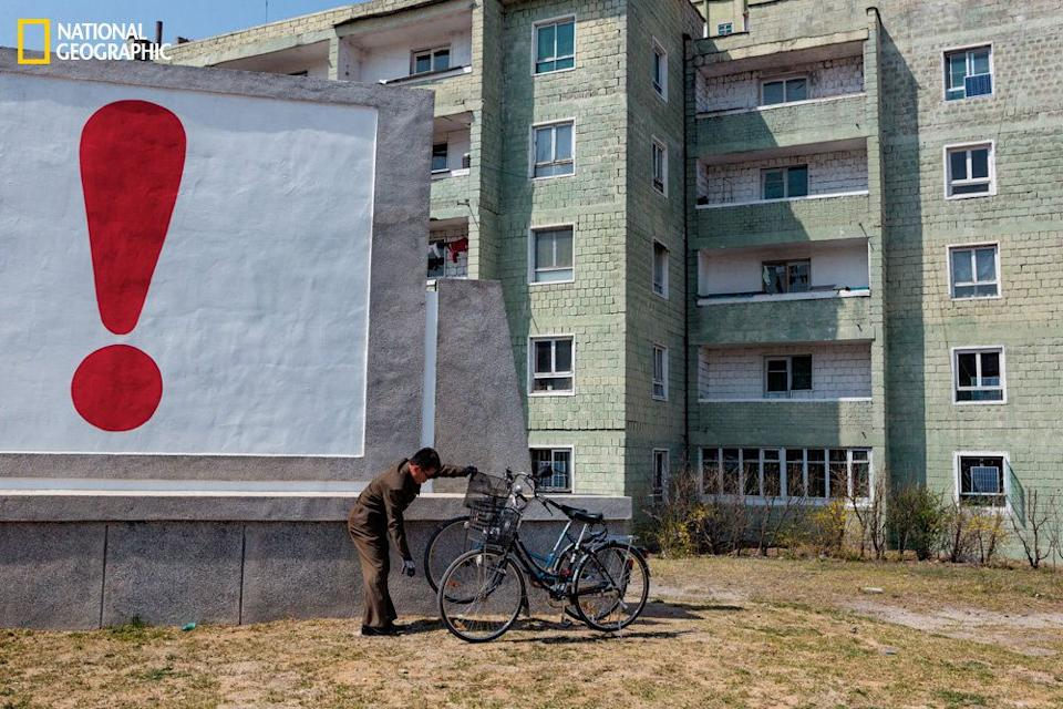 A man tends to his bicycle outside a housing complex in Kaesong, not far from the border with South Korea. An exclamation point at the end of an emphatic propaganda slogan punctuates the scene. (David Guttenfelder/National Geographic)