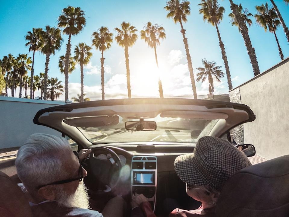 Senior trendy couple inside a convertible car - Mature people having fun doing a road trip in a tropical place - Travel, fashio and joyful elderly concept - Main focus on woman hat