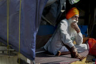 """Indian farmer Karnal Singh, 60, sits in the back of his tractor trolly as he camps with others against agricultural laws passed last year that they say will devastate their income, at Singhu, along the Delhi-Haryana border, Friday, March 5, 2021. For 100 days, Singh, has lived inside the back of a trailer, along a vast stretch of arterial highway that connects India's north with New Delhi. He camped outside the capital when it was under the grip of winter and smog filled the air. Now, New Delhi is bracing for a harsh summer where temperatures sometimes rise to 45 degree Celsius. """"We are not going anywhere and will fight till the end,"""" Singh said on Friday, as he sat cross-legged inside a makeshift shelter in the back of his truck. (AP Photo/Manish Swarup)"""