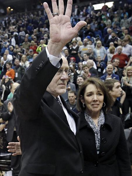 Minnesota Timberwolves head coach Rick Adelman waves to fans as his wife Mary Kay accompanies him after he became the eighth coach in the NBA to win 1,000 games after the Timberwolves' 107-101 win over the Detroit Pistons in a basketball game Saturday, April 6, 2013 in Minneapolis. (AP Photo/Jim Mone)