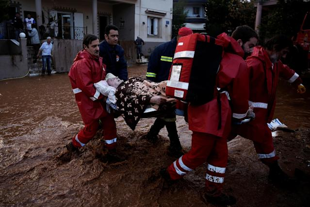 <p>Hellenic Red Cross volunteers and firemen evacuate an elderly man following heavy rainfall in the town of Mandra, Greece, Nov. 16, 2017. (Photo: Alkis Konstantinidis/Reuters) </p>
