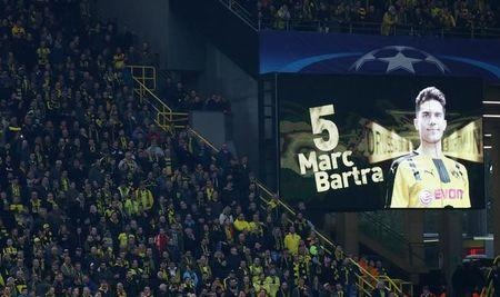 FILE PHOTO: Borussia Dortmund fans look on as a message is displayed in support of Borussia Dortmund's Marc Bartra