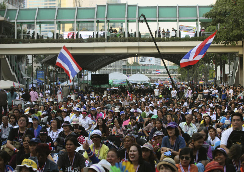 In this photo taken Jan. 15, 2014, anti-government protesters listen to a speech during a rally led by former deputy prime minister Suthep Thaugsuban at Ratchabrasong intersection in Bangkok, Thailand. Four years ago Suthep ordered a crackdown that saw the army rip through anti-government protesters' tire-and-bamboo-barricaded encampments and fire M-16s into crowds of fleeing protesters. Today, he is leading a protest movement that has itself blocked roads and broken into government offices - an extraordinary role reversal that underscores not only the cyclical nature of Thai politics, but the total lack of progress toward bridging a political divide that has plagued the country for nearly a decade. Among the places his supporters occupy is the place the Red Shirts made their last stand four years ago: Ratchaprasong, the country's glitziest intersection, where just like the Red Shirts, protesters are camping in the middle of the road, in front of a huge stage complete with speakers and a giant video screen. (AP Photo/Sakchai Lalit)