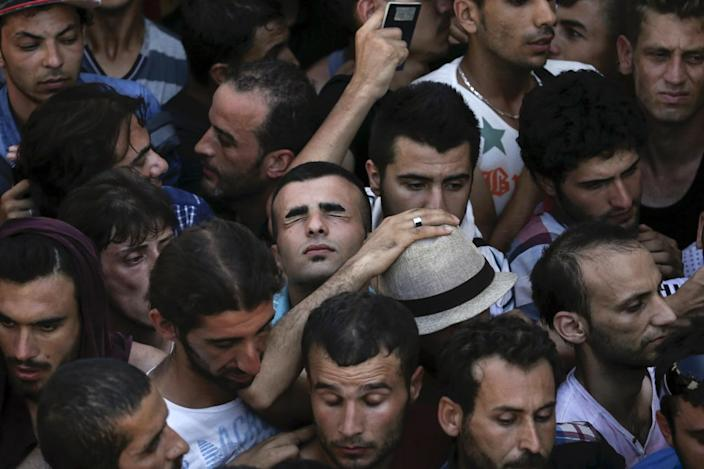<p>A Syrian refugee tries to catch his breath as he stands in a crowded line to get registered at the national stadium on the Greek island of Kos, Aug. 12, 2015. <i>(Alkis Konstantinidis/Reuters)</i></p>