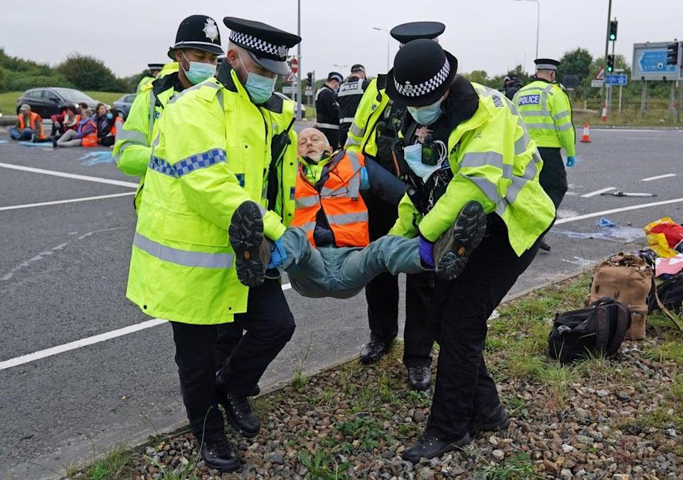 Police officers carry away an Insulate Britain  protester who had glued himself to the highway at a slip road at Junction 4 of the A1(M), near Hatfield (PA)