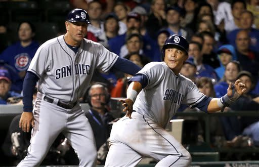 San Diego Padres third base coach Glenn Hoffman, left, sends Everth Cabrera back to third after a pitch by Chicago Cubs relief pitcher Shawn Camp did not get past catcher Welington Castillo during the seventh inning of a baseball game, Monday, April 29, 2013, in Chicago. (AP Photo/Charles Rex Arbogast)