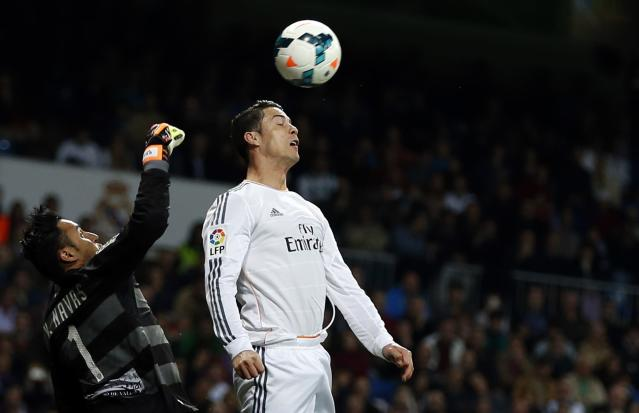 Real Madrid's Cristiano Ronaldo (R) and Levante's goalkeeper Keylor Navas fight for the ball during their Spanish first division soccer match at Santiago Bernabeu stadium in Madrid March 9, 2014. REUTERS/Sergio Perez (SPAIN)