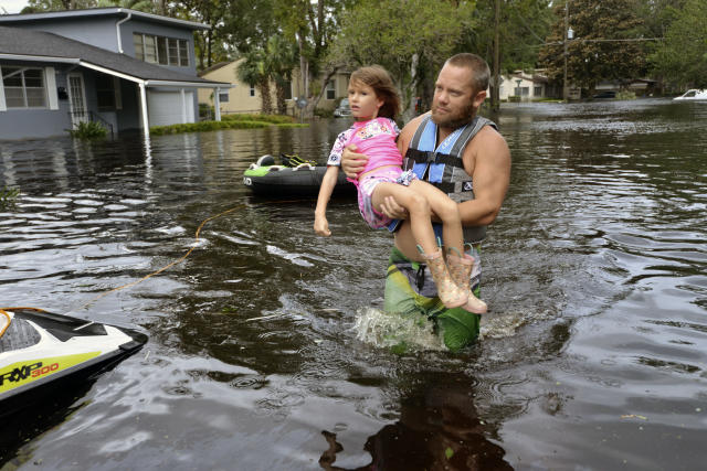 <p>Tommy Nevitt carries Miranda Abbott, 6, through floodwater caused by Hurricane Irma on the west side of Jacksonville, Fla., Sept. 11 2017. (Photo: Dede Smith/The Florida Times-Union via AP) </p>