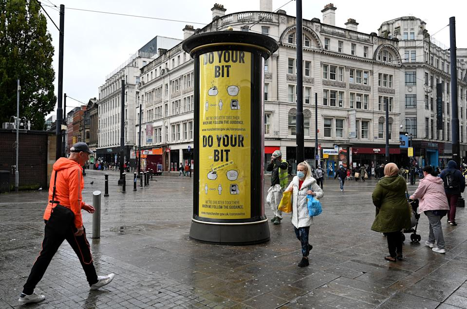 """A woman wearing a face mask or covering due to the COVID-19 pandemic, walks past a sign asking pedestrians to """"Do Your Bit"""" in Manchester, northern England on October 6, 2020, after localised restrictions were introduced across northwest following a spike in coronavirus cases. - More than 42,000 people confirmed to have Covid-19 have died in Britain, the worst toll in Europe. (Photo by Paul ELLIS / AFP) (Photo by PAUL ELLIS/AFP via Getty Images)"""