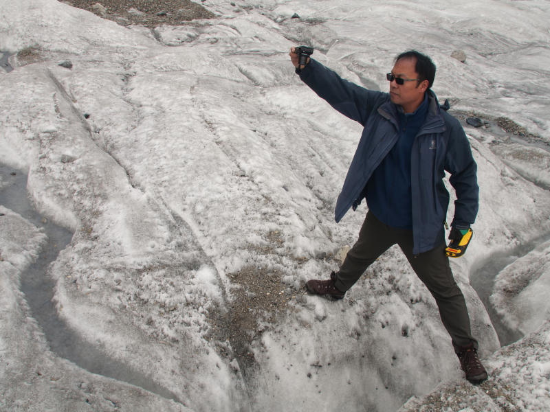 This Sept. 22, 2018 photo shows glaciologist Wang Shijin photographing an ice crevasse in the Baishui Glacier No. 1 on the Jade Dragon Snow Mountain in the southern province of Yunnan in China. Scientists say the glacier is one of the fastest melting glaciers in the world due to climate change and its relative proximity to the Equator. It has lost 60 percent of its mass and shrunk 250 meters since 1982. (AP Photo/Sam McNeil)