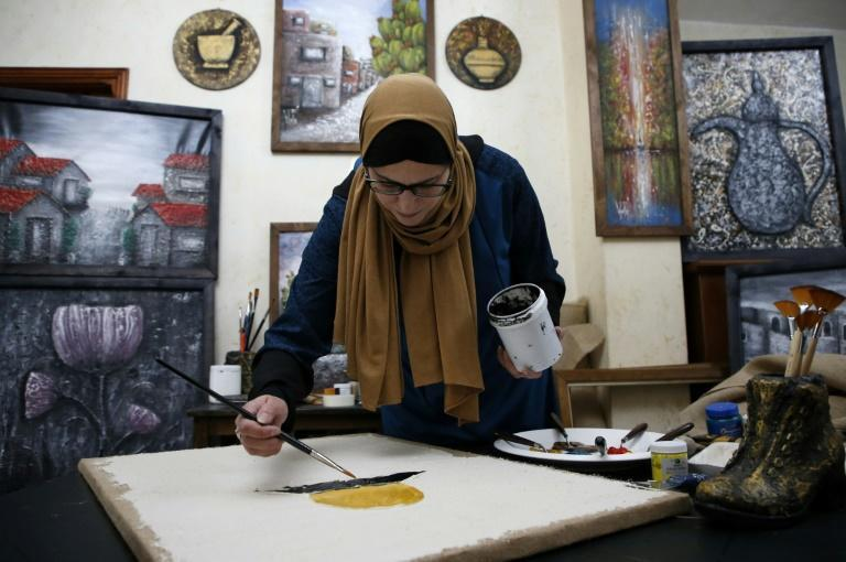 Wafaa al-Adhami, 46, a Palestinian artist and mother, paints at her home in the West Bank town of Hebron