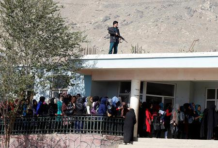 Afghan women line up to cast their votes, as a policeman keeps watch on the roof during the parliamentary election at a polling station in Kabul, Afghanistan October 21, 2018. REUTERS/Omar Sobhani