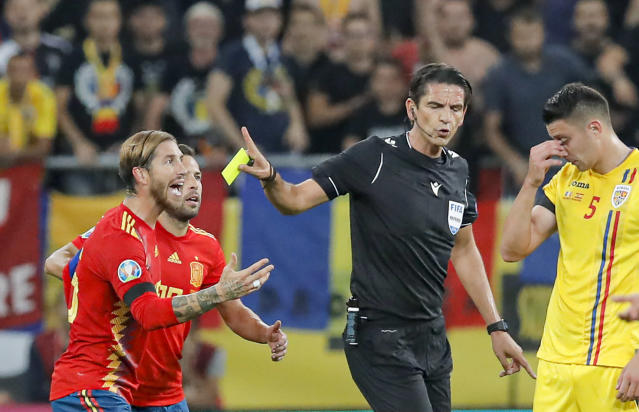 Spain's Sergio Ramos, left reacts after being yellow carded during the Euro 2020 group F qualifying soccer match between Romania and Spain, at the National Arena stadium in Bucharest, Romania, Thursday, Sept. 5, 2019. (AP Photo/Vadim Ghirda)