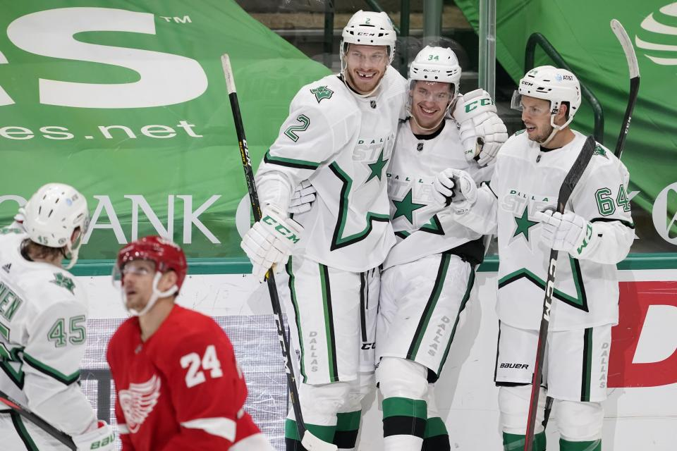 Detroit Red Wings right wing Richard Panik (24) skates past as Dallas Stars' Sami Vatanen (45), Jamie Oleksiak (2), Denis Gurianov (34) and Tanner Kero (64) celebrate a goal scored by Oleksiak in the second period of an NHL hockey game in Dallas, Tuesday, April 20, 2021. (AP Photo/Tony Gutierrez)
