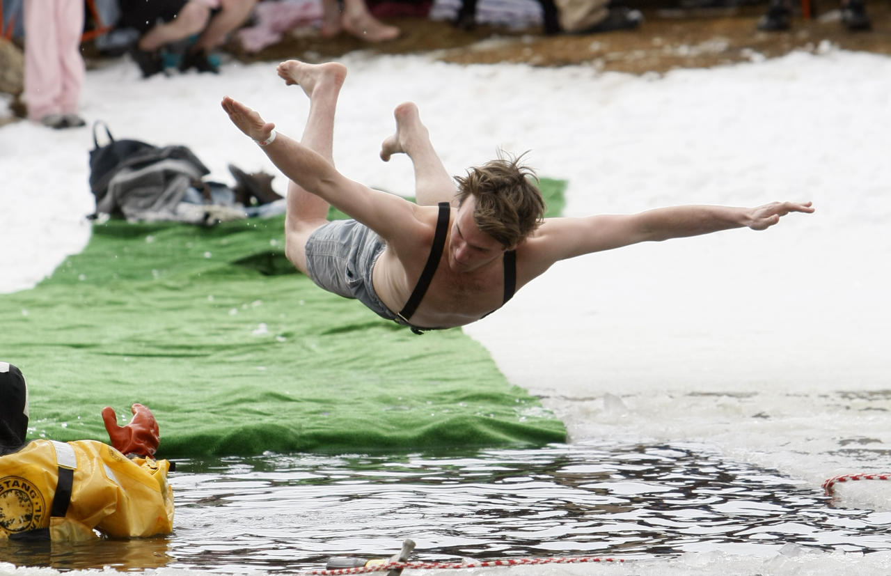 A man competes in the Polar Plunge, by jumping into a hole cut in the ice covering a lake, during Frozen Dead Guys Days in Nederland, Colorado March 8, 2008. REUTERS/Rick Wilking