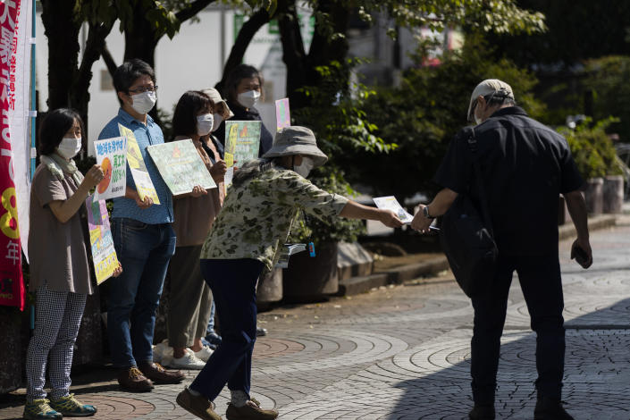 """Kimiko Toko, center, the leader of the Kodaira Solar, hands out a flyer during a demonstration to promote community-oriented solar energy power plants, outside a train station in Kodaira, west of Tokyo, Friday, Sept. 24, 2021. The Kodaira group, a nonprofit organization, was in solidarity with the Fridays for Future climate movement calling for the """"global day of climate action."""" (AP Photo/Hiro Komae)"""