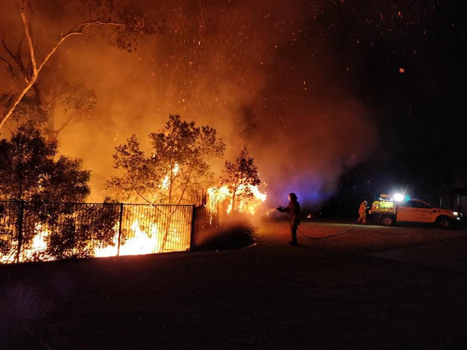 A person holds a hose up to a burning fence at night in Queensland.