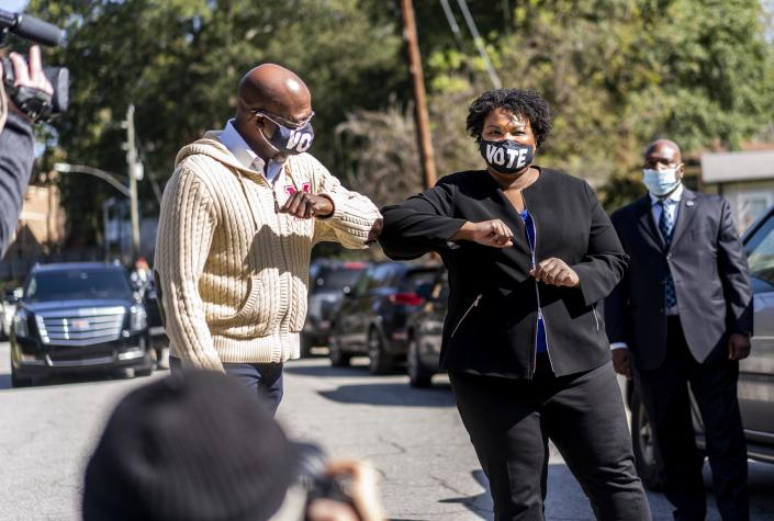 Democratic U.S. Senate candidate Rev. Raphael Warnock, pastor of Ebenezer Baptist Church, and Stacey Abrams speak to voters in Atlanta. (Melina Mara/The Washington Post via Getty Images)