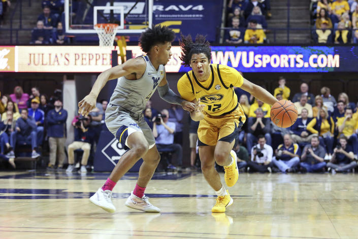 Missouri guard Dru Smith (12) drives it up court as he is defended by West Virginia guard Miles McBride (4) during the first half of an NCAA college basketball game Saturday, Jan. 25, 2020, in Morgantown, W.Va. (AP Photo/Kathleen Batten)