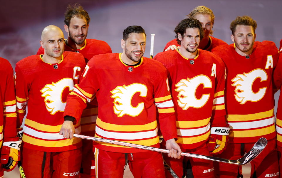 Calgary Flames' Milan Lucic, center, holds a silver stick as he poses with his teammates celebrating his 1000th NHL game before facing the Ottawa Senators, in Calgary, Alberta, Monday, April 19, 2021. (Jeff McIntosh/The Canadian Press via AP)