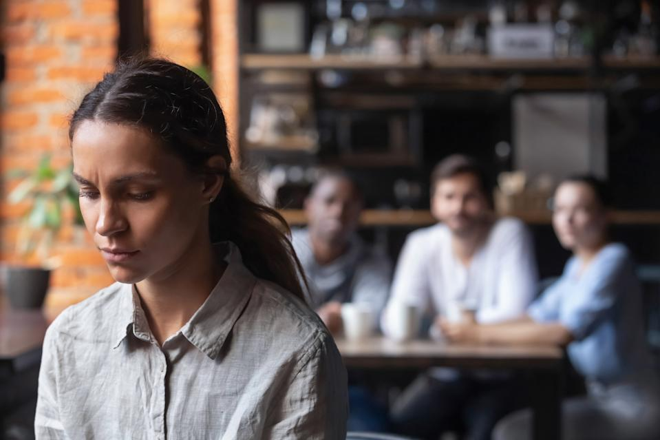 Upset mixed race woman suffering from bullying, discrimination, excluded girl having problem with bad friends, feeling offended and hurt, sitting alone in cafe, avoiding people, social outcast