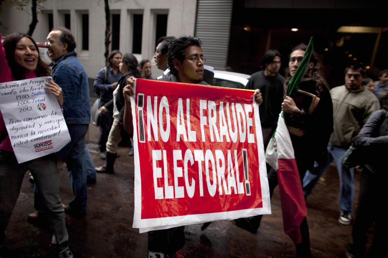 "A man holds up a sign that reads in Spanish ""No to electoral fraud"" outside a hotel where Mexican presidential candidate Andres Manuel Lopez Obrador of the Democratic Revolution Party (PRD), gave a news conference in Mexico City, Monday, July 2, 2012. After official results showed Enrique Pena Nieto of the Institutional Revolutionary Party (PRI) winning 38 per cent of the vote with more than 92 per cent of the votes counted, Lopez Obrador has not conceded Sunday's elections,  telling his  supporters Monday evening that, ""We can't accept a fraudulent result,"" a reference to his allegations that Pena Nieto exceeded campaign spending limits, bought votes in some states and benefited from favorable coverage in Mexico's semi-monopolized television industry. (AP Photo/Alexandre  Meneghini)"