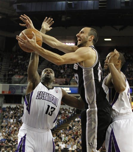 San Antonio Spurs forward Manu Ginobili, center, of Argentina, drives to the basket between Sacramento Kings' Tyreke Evans, left, and Chuck Hayes during the first quarter of an NBA basketball game in Sacramento, Calif., Wednesday, April 18, 2012. (AP Photo/Rich Pedroncelli)