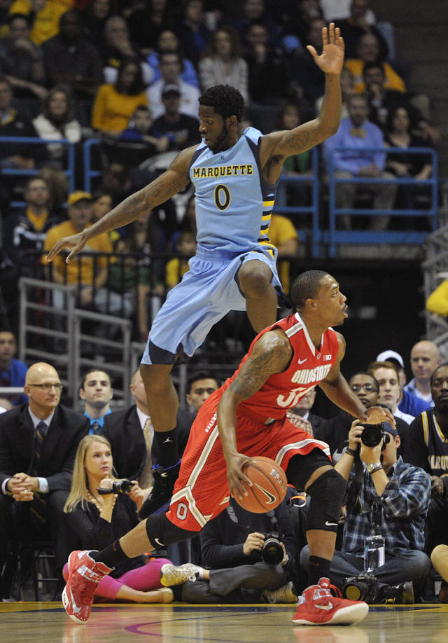 Marquette's Jamil Wilson (0) flies through the air trying to block the shot of Ohio State's' Lenzelle Smith Jr. during the first half of an NCAA college basketball game Saturday, Nov. 16, 2013, in Milwaukee. (AP Photo/Jim Prisching)