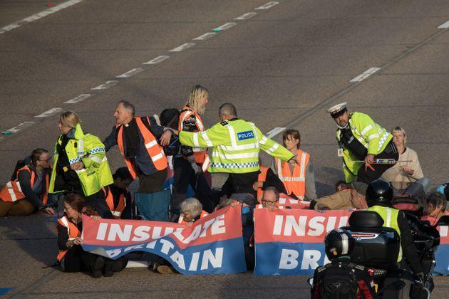 <strong>Surrey Police officers try to remove Insulate Britain climate activists from the carriageway.</strong> (Photo: Mark Kerrison via Getty Images)