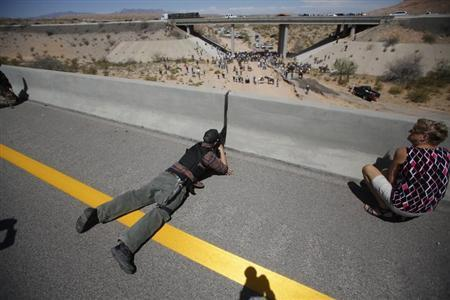 Eric Parker from central Idaho aims his weapon from a bridge as protesters gather by the Bureau of Land Management's base camp, where cattle that were seized from rancher Cliven Bundy are being held, near Bunkerville, Nevada April 12, 2014. REUTERS/Jim Urquhart