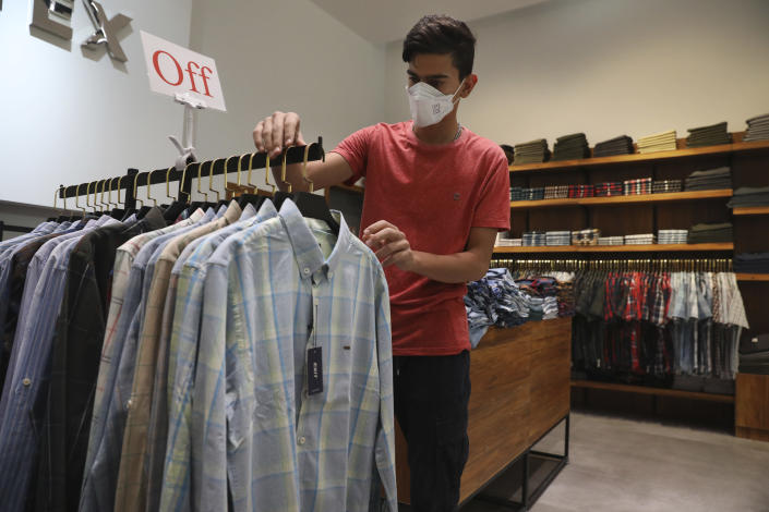 A shopkeeper arranges clothing in a men's clothing store at Iran Mall shopping center in Tehran, Iran, Wednesday, June 9, 2021. The West considers Iran's nuclear program and Mideast tensions as the most important issues facing Tehran, but those living in the Islamic Republic repeatedly point to the economy as the major issue facing it ahead of its June 18 presidential election. (AP Photo/Vahid Salemi)