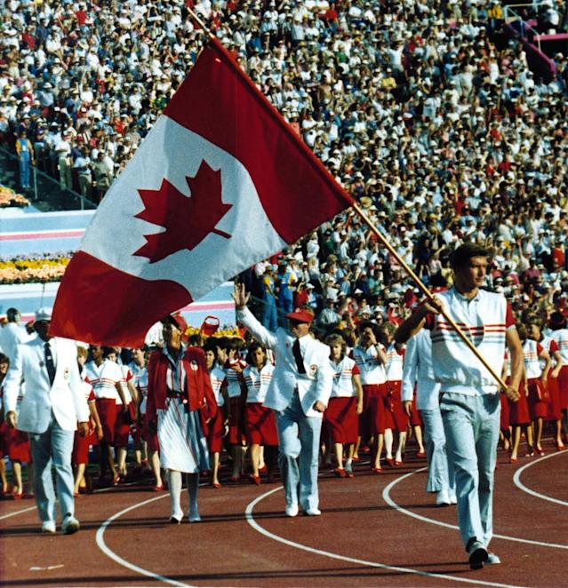 Swimmer Alex Baumann carries the Canadian flag as the team follows behind him during the opening ceremonies for the Los Angeles Summer Olympics, July 29, 1984. (CP PHOTO/Gary Hershorn)