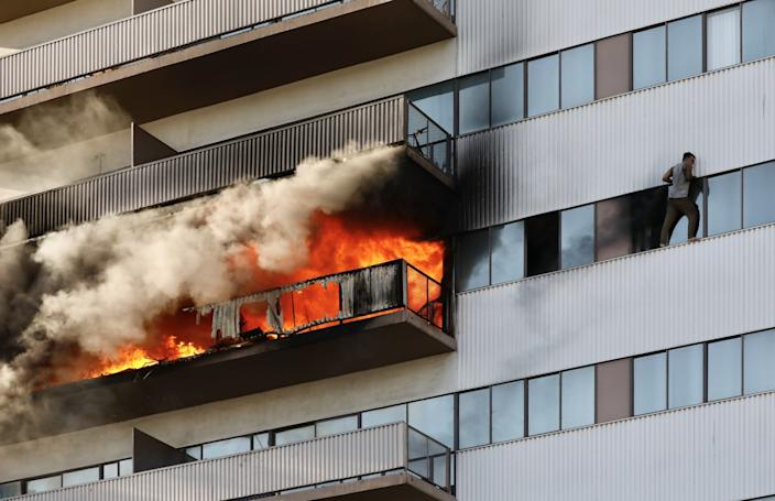 A resident, arms blackened, stands on the ledge of a window several stories up. Fire rages on a balcony near him.
