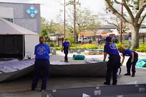 A Disaster Medical Assistance Team sets up tents at Lake Charles Memorial Hospital to provide support in response to Hurricane Laura. Responders like these are processed using F/ERO ATS. FEMA photo