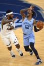 Memphis Grizzlies guard Ja Morant (12) tries to get past the defense of Utah Jazz forward Royce O'Neale during the first half of Game 3 of an NBA basketball first-round playoff series Saturday, May 29, 2021, in Memphis, Tenn. (AP Photo/John Amis)