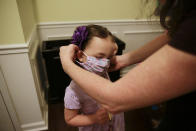 FILE - In this Aug. 3, 2020, file photo, Rachel Adamus, right, helps her daughter Neva, 5, put on her mask before her first day of kindergarten in Dallas, Ga. As schools reopen around the country, their ability to quickly identify and contain coronavirus outbreaks before they get out of hand is about to be put to the test. (AP Photo/Brynn Anderson, File)