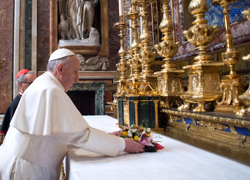 CORRECTS YEAR TO 2013 - In this photo provided by the Vatican newspaper L'Osservatore Romano, Pope Francis puts flowers on the altar inside St. Mary Major Basilica, in Rome, Thursday, March 14, 2013. Pope Francis opened his first morning as pontiff by praying Thursday at Rome's main basilica dedicated to the Virgin Mary, a day after cardinals elected him the first pope from the Americas in a bid to revive a Catholic Church in crisis and give it a preacher with a humble touch. (AP Photo/L'Osservatore Romano, ho)