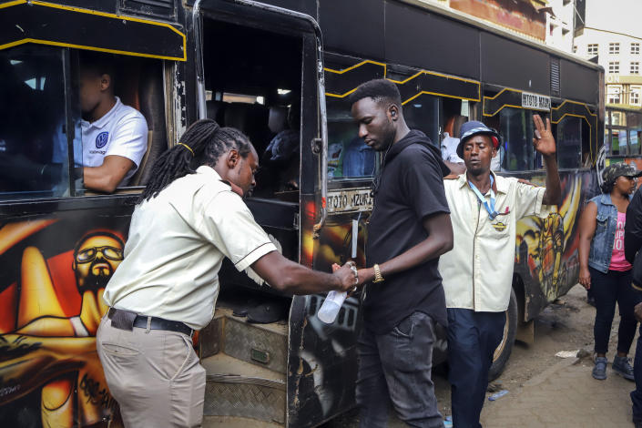 """A bus conductor disinfects the hands of a passenger, after the government directed all operators of """"matatus"""", or public minibuses, to provide hand sanitizer to their clients, on a busy street in downtown Nairobi, Kenya Friday, March 13, 2020. Authorities in Kenya said Friday that a Kenyan woman who recently traveled from the United States via London has tested positive for the new coronavirus, the first case in the East African country. (AP Photo/Patrick Ngugi)"""