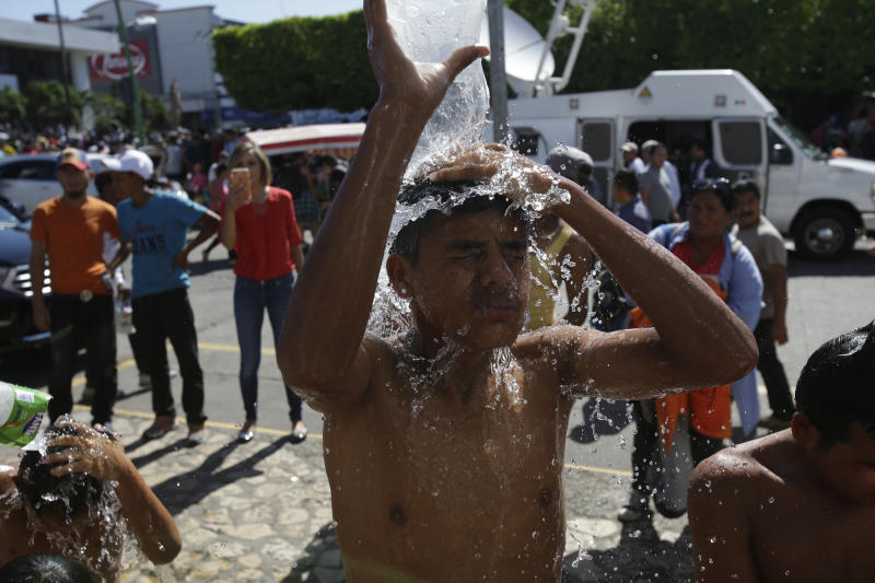 Central American migrants making their way to the U.S. in a large caravan bathe using water from a fire hydrant at the main plaza in Tapachula, Mexico, Monday, Oct. 22, 2018. Thousands of Central American migrants hoping to reach the U.S. were deciding Monday whether to rest in this southern Mexico town or resume their arduous walk through Mexico as President Donald Trump rained more threats on their governments. (AP Photo/Moises Castillo)