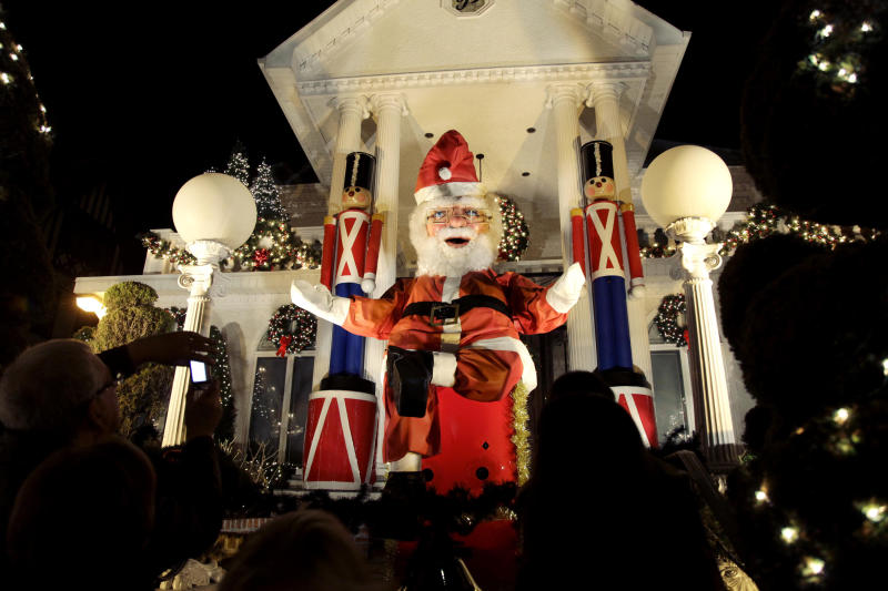 "This Dec. 4, 2012 photo shows spectators viewing a a giant Santa Claus at a decorated home in the Brooklyn borough of New York. Each holiday season, tour operator Tony Muia takes tourists from around the world on his ""Christmas Lights & Cannoli Tour"" visiting the Brooklyn neighborhoods of Dyker Heights and Bay Ridge, where locals take pride in over-the-top holiday light displays.  (AP Photo/Seth Wenig)"