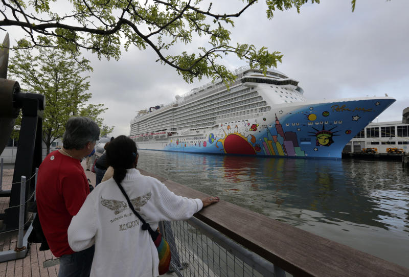 FILE - This May 8, 2013 photo shows people pausing to look at the Norwegian Cruise Line's new ship, Norwegian Breakaway, on the Hudson River, in New York. The ship has a colorful mural on the exterior hull design by pop artist Peter Max featuring the city skyline and the Statue of Liberty. The 2013 cruise season began with a nightmare: A Carnival ship adrift with no power. But in the last month or so, several cruise companies have announced major overhauls to old ships and exciting innovations on new ships, from engineering upgrades to theme park-style rides. (AP Photo/Richard Drew, file)