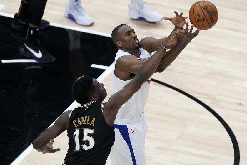 Los Angeles Clippers center Serge Ibaka (9) and Atlanta Hawks center Clint Capela (15) battle for a loose ball in the second half of an NBA basketball game Tuesday, Jan. 26, 2021, in Atlanta. (AP Photo/John Bazemore)