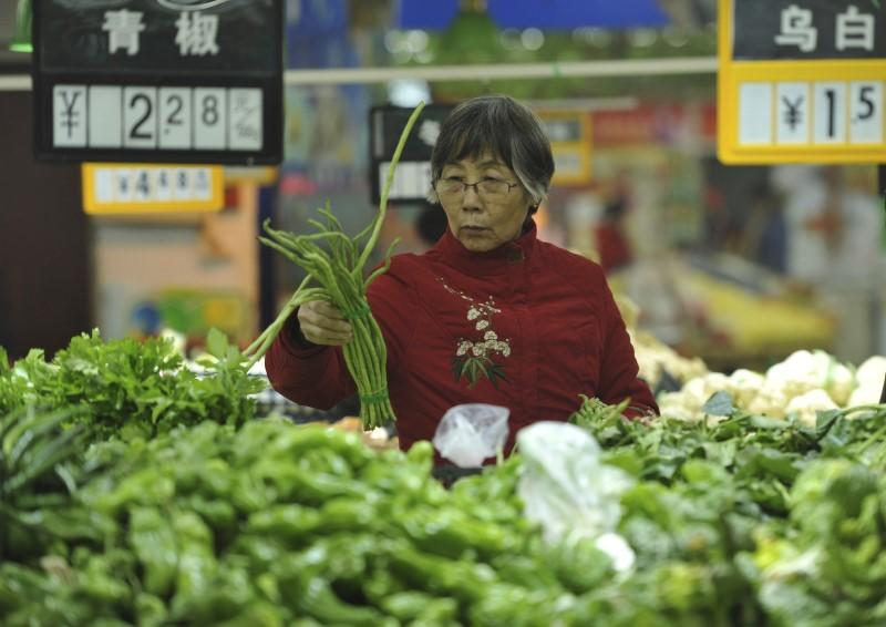 A customer selects vegetable at a supermarket in Fuyang