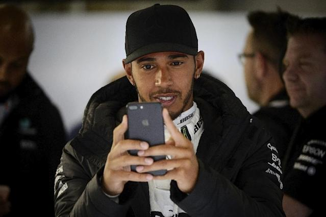 Mercedes' British driver Lewis Hamilton looks at his mobile phone during the second practice session ahead of the Formula One Chinese Grand Prix in Shanghai on April 7, 2017 (AFP Photo/WANG ZHAO)