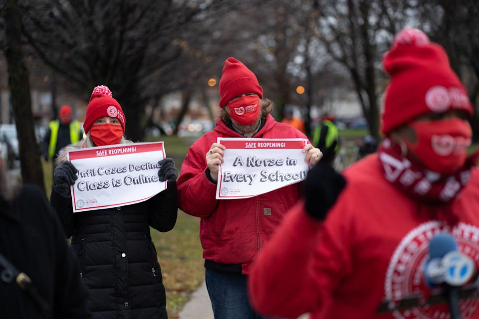 Chicago Teachers Union members display signs while former teacher Tara Stamps speaks ahead of a car caravan where teachers and supporters gathered to demand a safe and equitable return to in-person learning during the COVID-19 pandemic in Chicago, IL on December 12, 2020. (Max Herman/NurPhoto via Getty Images)