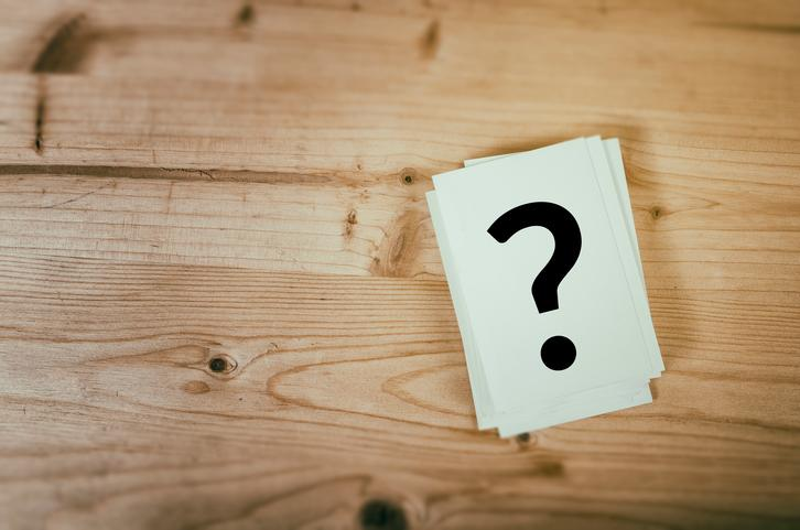 A question mark drawn on a card that is sitting on a wooden surface.