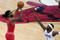 Chicago Bulls guard Coby White, left, shoots over Los Angeles Clippers guard Reggie Jackson during the first half of an NBA basketball game in Chicago, Friday, Feb. 12, 2021. (AP Photo/Nam Y. Huh)