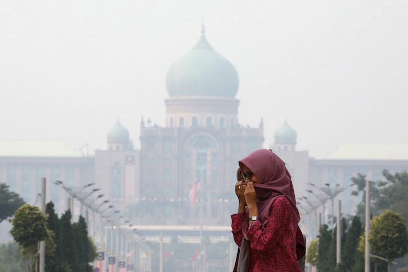 A woman covers her face with a scarf in front of the Prime Minister's Office, which is shrouded in haze, in Putrajaya September 17, 2019. — Reuters pic